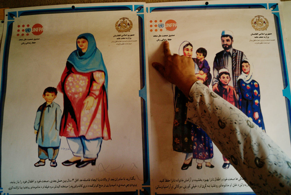 Afghanistan, Katuq, August 2008, Traditional Birth Attendant Osima points to information on a poster distributed UNFPA alerting women to family planning issues pinned to the wall of the health post where she works in Katuq Village.