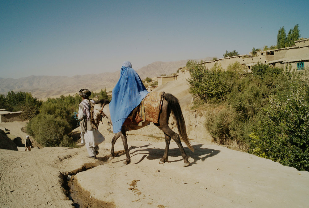 Afghanistan, Shahr-I-Buzorg, August 2008, Travelling with her baby Hamza under her burka, wenty five year old Faroza is lead by her father as she is escorted along the rough roads of Badakshan on the way to Shahr-i-Buzorg's health post. Having given birth two months ago, Faroza's husband went to the pharmacy for her but could find little advice and the drugs he bought had no effect. She has been bleeding ever since. After the two hour unconfortable journey, they are told that Faroza has liver damage- a possible side effect of the drugs and that she could have problems with future deliveries.
