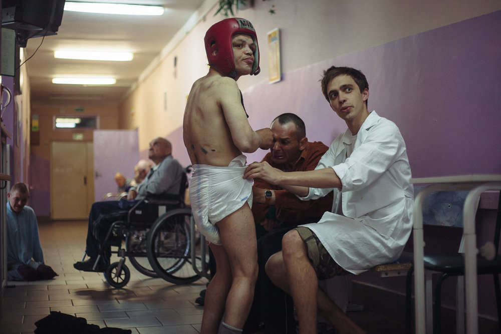 Nursing assistant is changing diaper of a resident of the resident care facility. May 24, 2016, Minsk, Belarus.