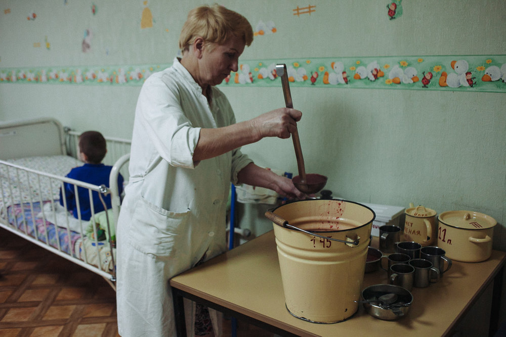 Nurse of the orphanage for disabled children with special psychophysical development is serving food for children. October 10, 2016, Minsk, Belarus.