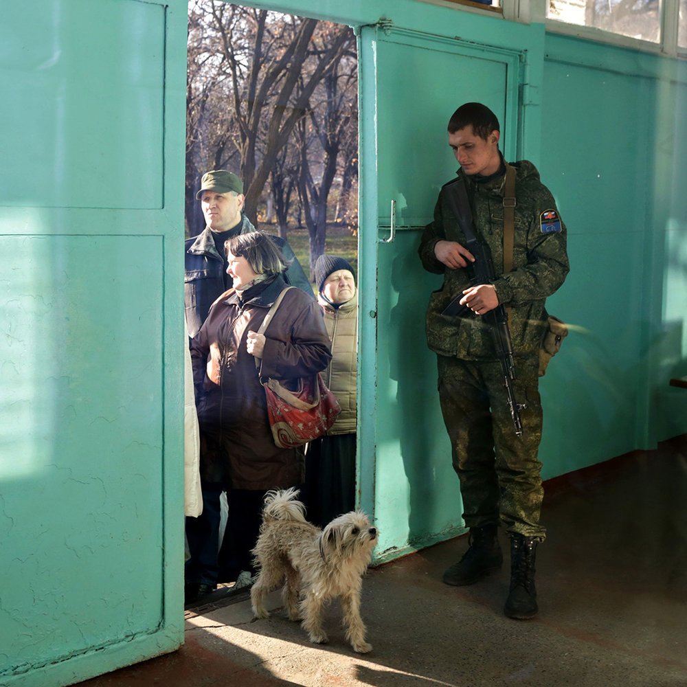 A Russian-backed insurgent guards the polling station on the election day in Donetsk, Ukraine.