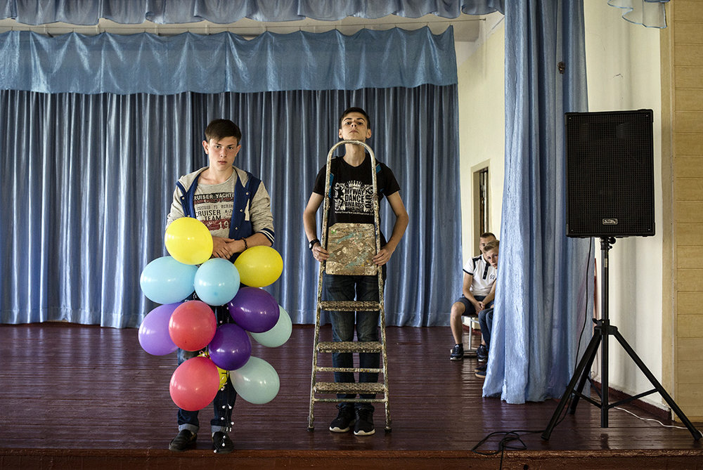 Classmates, Ilya Gudzovatiy and Ilya Shlykov, decorate the school's assembly hall in Shchastya, Luhansk area, Ukraine. 