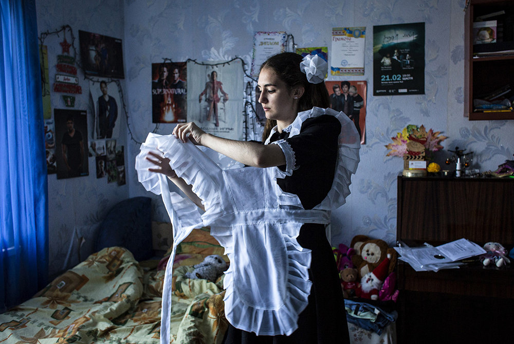 Anastasia Sarancha, 17, gets dressed for her graduation day in Shchastya, Ukraine.