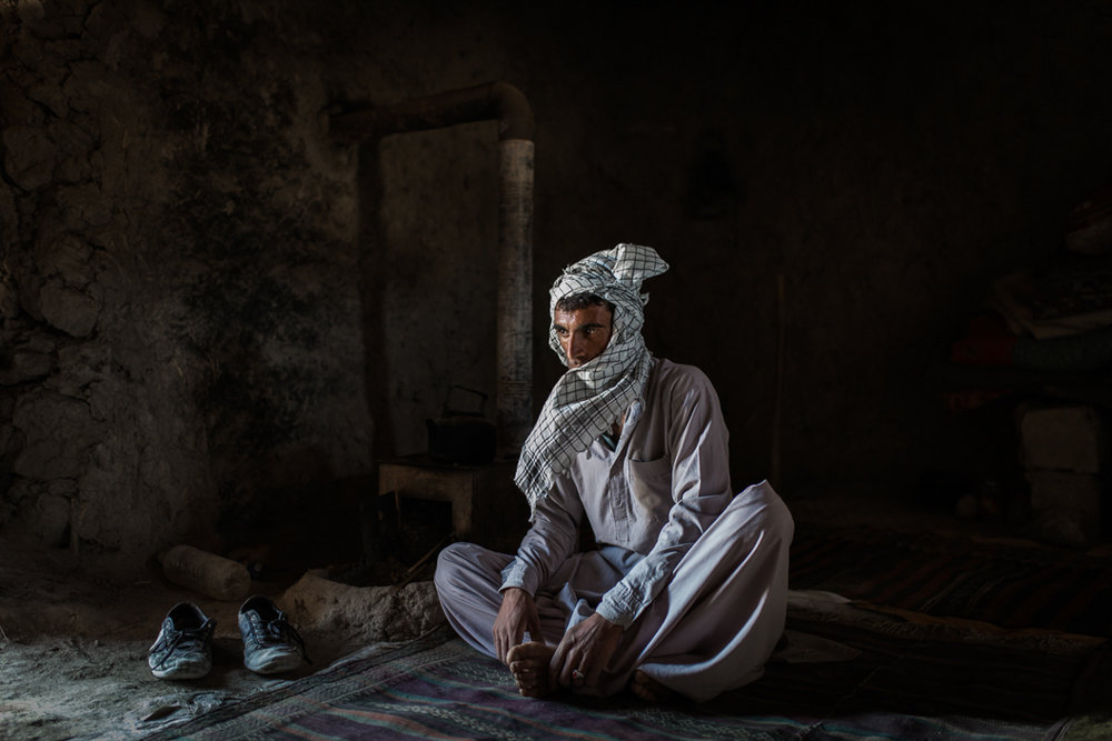 A shepherd poses for a portrait in his small room in a fishing village near Zabol.