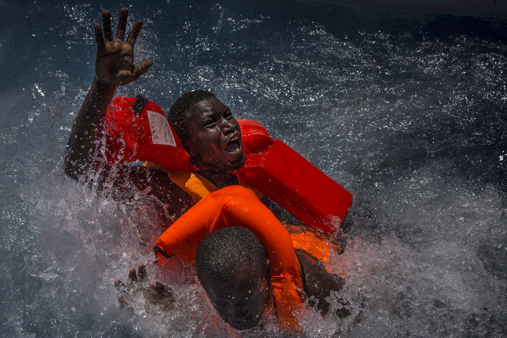 Two men panic and struggle in the water during their rescue. Their rubber boat was in distress and deflating quickly on one side, tipping many migrants in the water. They were quickly reached by rescue swimmers and brought to safety.  � Mathieu Willcocks/MOAS.eu 2016, all rights reserved.