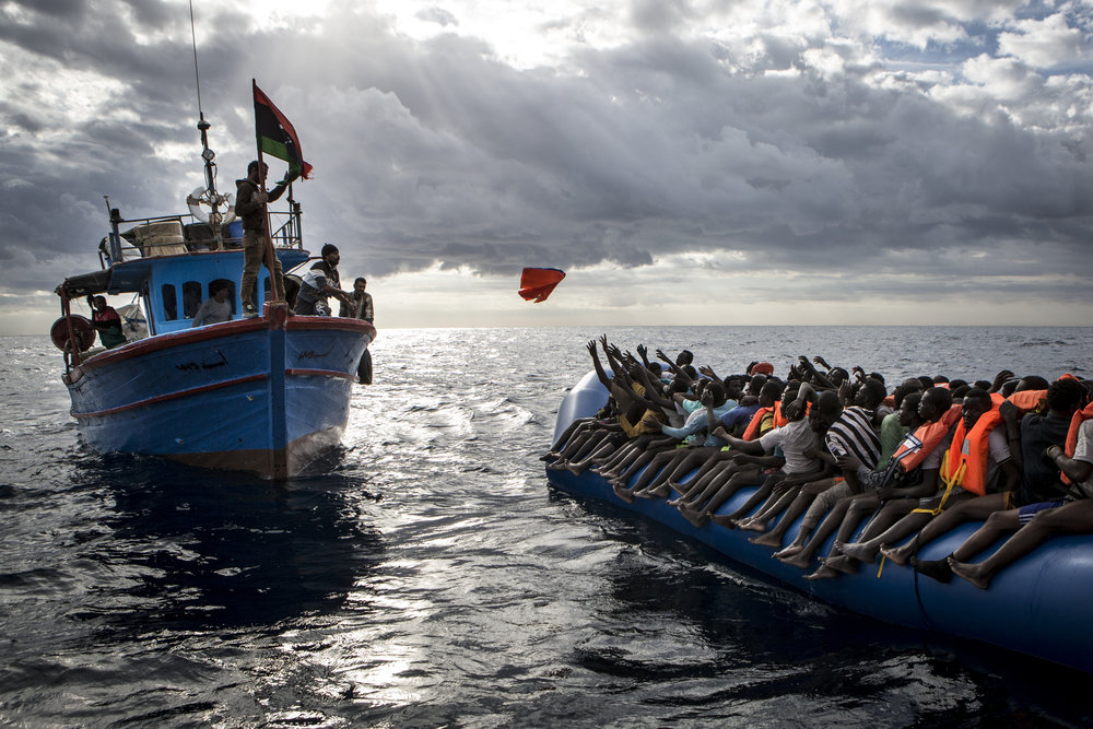 Libyan fishermen throw a lifejacket at a rubber boat full of migrants. In the vast majority of cases, smugglers to not provide migrants with life jackets.