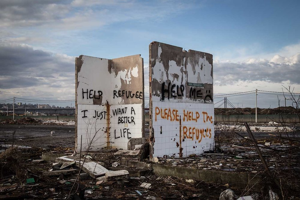 """Graffiti on breached walls inside the """"Barracks"""", an abandoned industrial complex where nearly 1,300 refugees have sought refuge as they wait to cross into Europe."""
