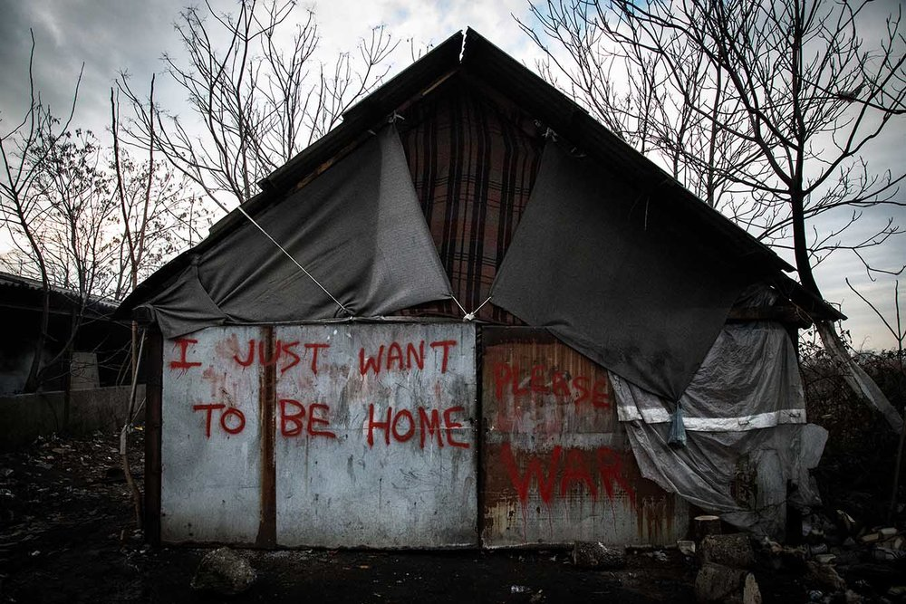 """A metail shack with graffiti reading """"I just want to be home."""", inside the abandoned industrial complex turned into makeshift refugee camp, in the area of Belgrade's Central Station."""