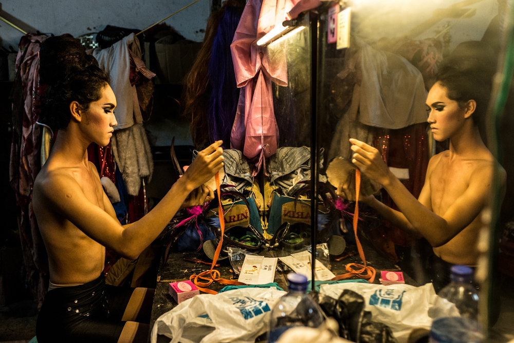 Dimas, a young waria performer, 17, is getting ready for her show, in the dressing room of Moonlight discoteque. Jakarta, Indonesia, 21st April, 2015.