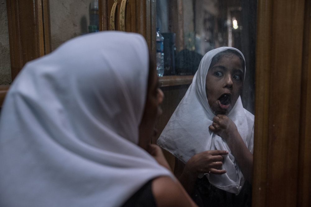 Fatma, wearing a costume hijab, makes goofy faces in the mirror. She is now 8 years old and in a couple of years, she will have to start covering her hair. 