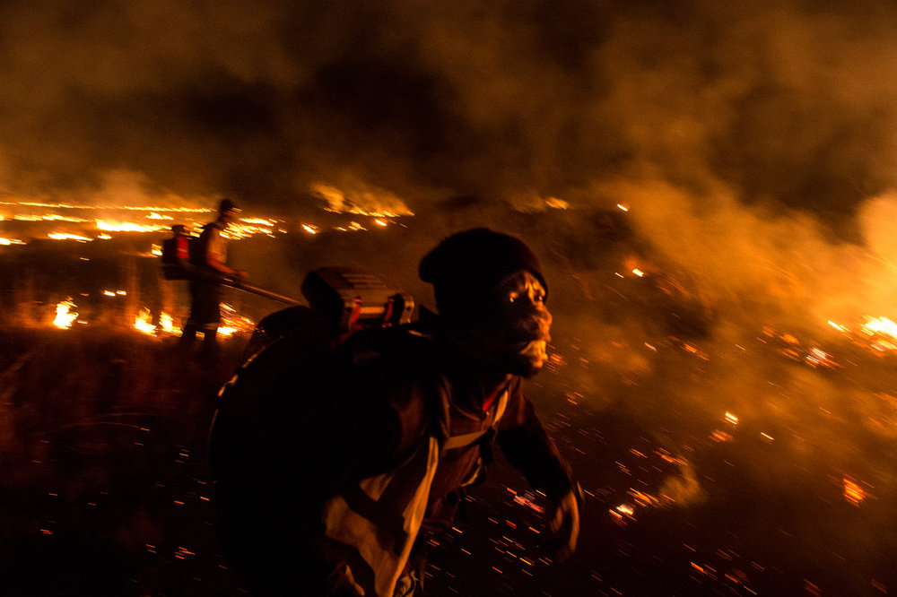 South Africa, Gauteng, 20.07.2018 // Farmers and farmworkers are  fighting  fires on their land. It's the third  fire this night. They assume the  fires are set.