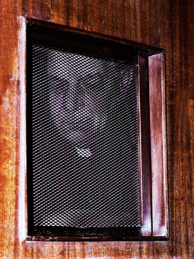 Don Monni in his parish confessional. Mamoiada, Barbagia.