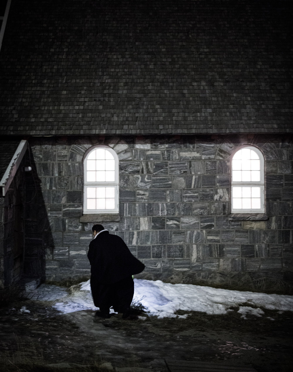 """The Greenlandic priest of the Lutheran Church of Greenland in Uummannaq is walking toward his chapel on the First Advent. He is one of the only confidants that the town's population can rely on. """"When the light changes, people look inwards, sometimes developing bad thoughts"""", he says later."""