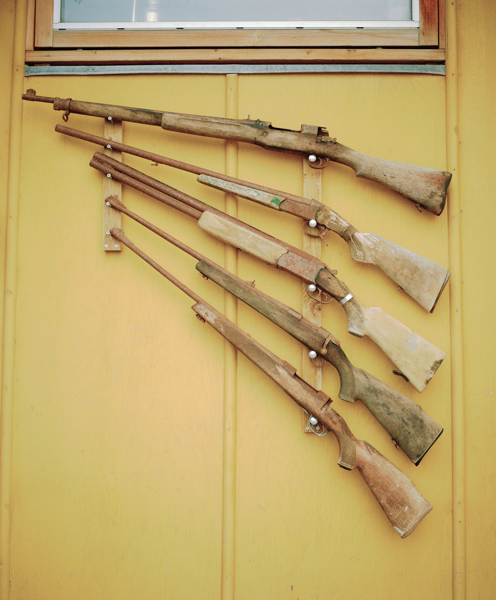 Old guns hang on the outside of a house in Uummannaq. Hunting is an old tradition, but the modern way of fishing provides more income because seal fur is no longer popular within the country or for exportation.