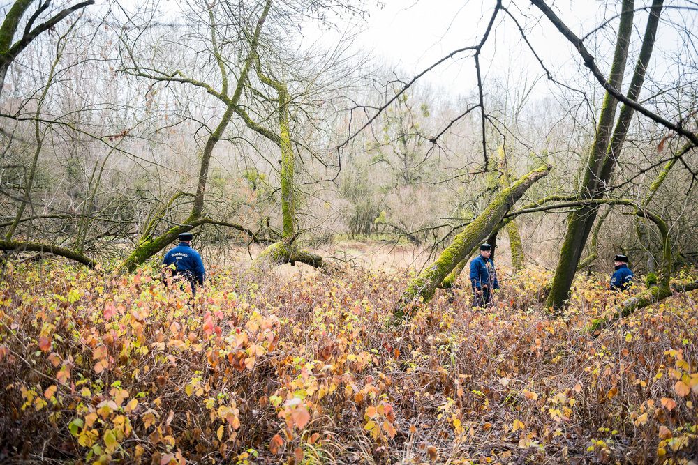 Policemen looking for signs of migrants near the barbed wire fence in the flood basin of Danube near Kölked, Hungary 9 December 2017. The fence was constructed in the middle of the European migration crisis in 2015, with the aim to ensure border security by preventing immigrants from entering the country and the European Union illegally.