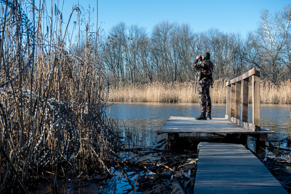 Woman soldier searching over  Ferenc main channel at the end of the barbed wire fence between Hungary and Serbia near Hercegszántó, Hungary 24 December 2017.  The fence was constructed in the middle of the European migration crisis in 2015, with the aim to ensure border security by preventing immigrants from entering the country and the European Union illegally.