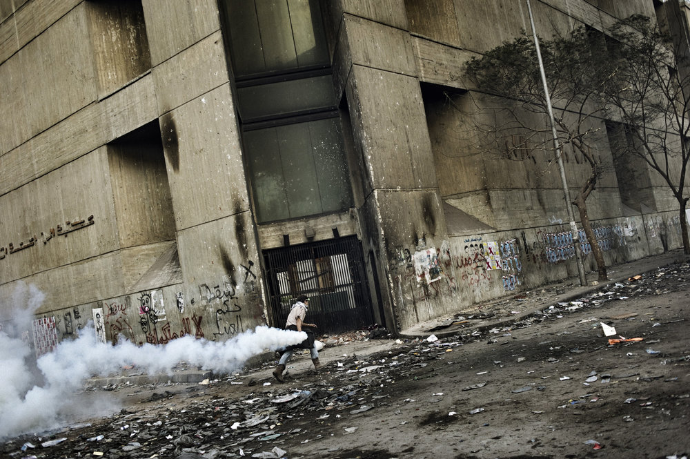 Cairo  Egypt November 23, 2011: A protester runs with a tear gas canister along Mohamed Mahmoud street, November 23, 2011.