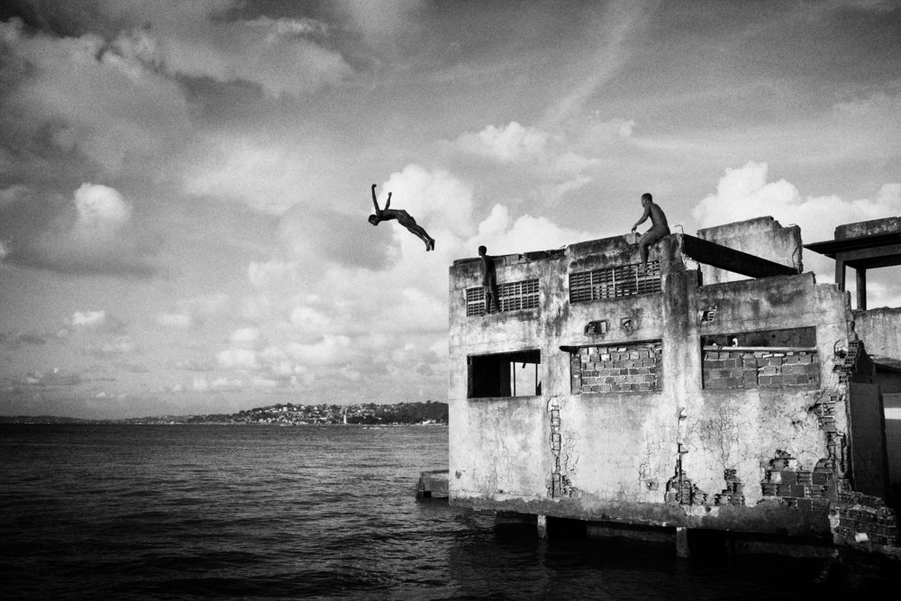 Brazil, Salvador de Bahia, March 2011, A boy jumping from a building of the abandoned chocolate factory.