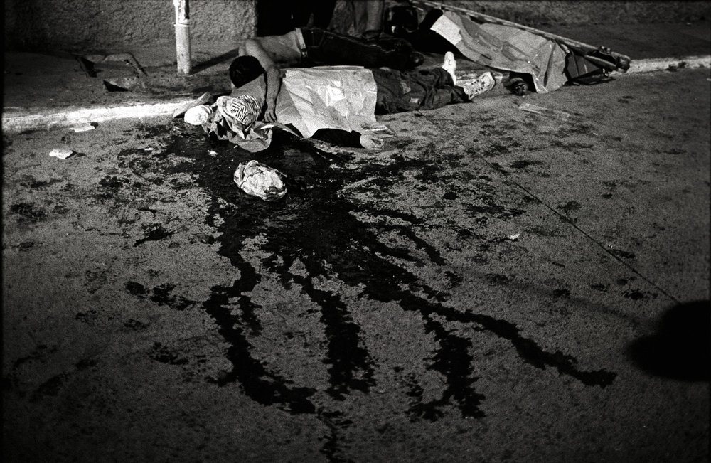 Guatemala, Guatemala City, April 2010, A man lies on top of the body of his murdered brother in Zone 6. Zone 6 is considered a red zone or dangerous zone where murders are common and life is quite cheap. The shooting occurred at the end of a wake for another shooting that had happened several days before.