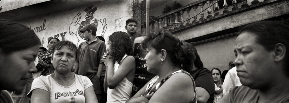 Guatemala, Guatemala City, July 2008, A family mourns for the loss of their loved one lying in a body bag on the outskirts of Guatemala City. The man was found in a ditch on the side of the road and had been there for some time before a street cleaner found him.