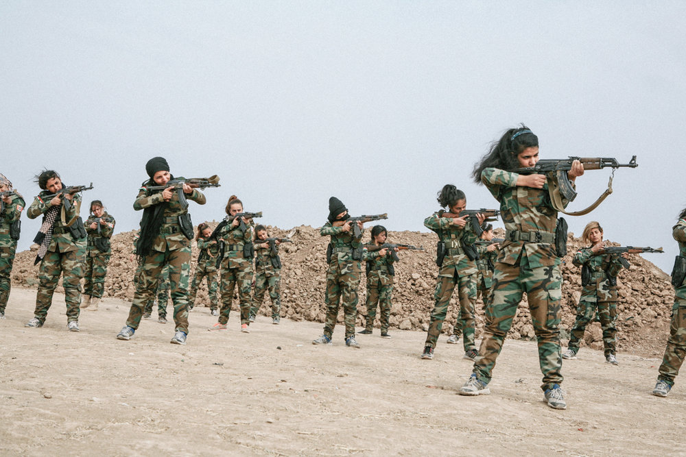 The young girls from PAK are training 6 km from Mosul, they feel happy that they are embodying the image of the strong and independent soldier who has been sold to them, they will not go to the fight. Bashiqa, Iraq, October 2016.