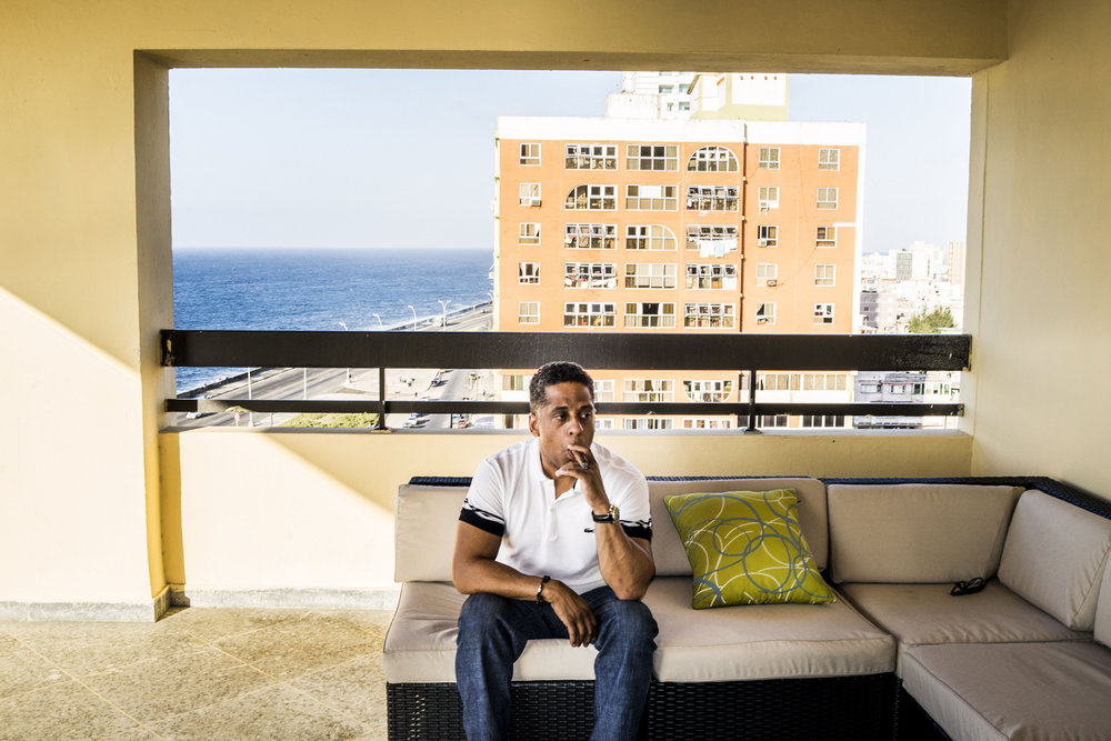 Havana, Cuba - February, 2015: Hugo Cancio, CEO of the OnCuba Magazine in his apartment balcony in Havana. For the first time in fifty years the United States and Cuba would restore ties and seems that the life conditions for Cubans will improve after decades of economical austerity.