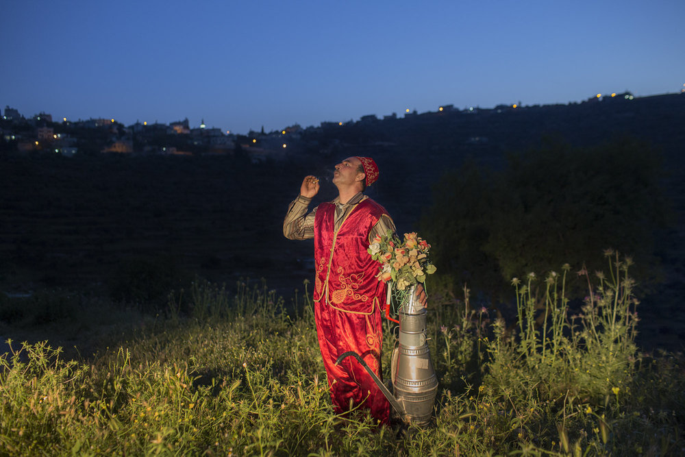 Occupied Palestinian Territories, West Bank, Abwein, 29 May 2015A coffee seller in traditional dress takes a break for a smoke, in Abwein on the West Bank.