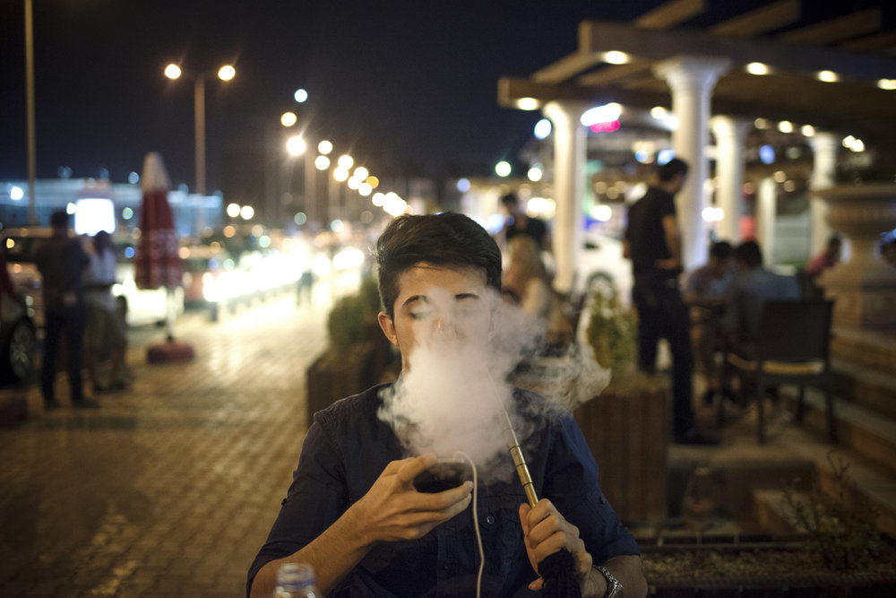 """Erbil, Iraq - Teens smoke sheesha in the upscale neighborhood of """"Dream City"""" in Erbil.Kurds in Iraq like to think of themselves as something completely distinct from the rest of Iraq--different than the Iraq of inflamed descent and sectarian issues. Foreign investor's interest in Kurdistan's oil has made this difference visible in the rich facade one can see daily in cities like Erbil."""