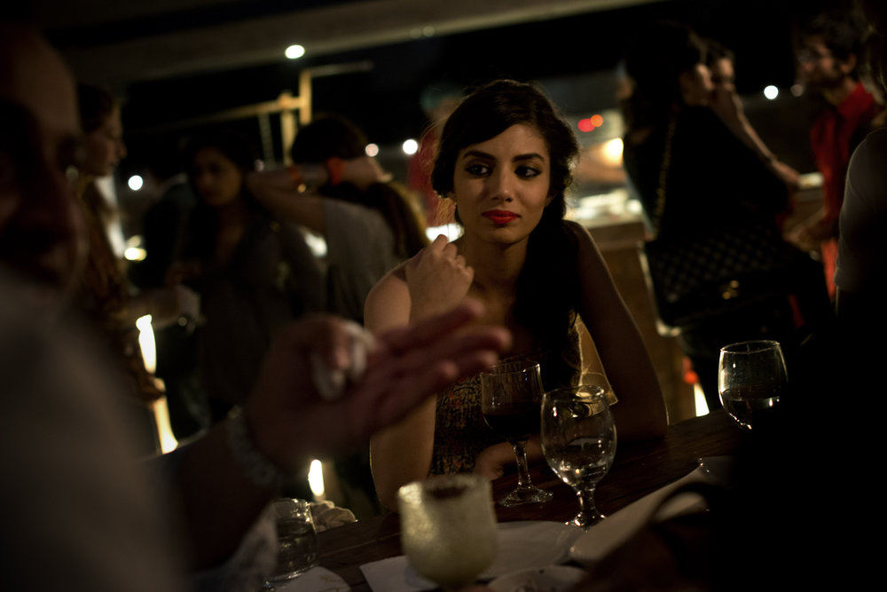 Models sip wine at a fashion show after party in Lahore.