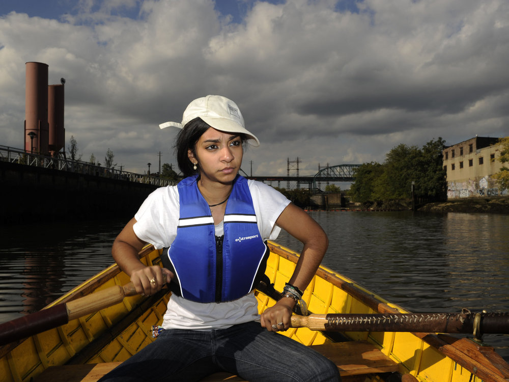"""Danise Infante, a high school student,  rows a boat she helped build, in the Bronx River.   She built the boat at an after school program called  """"Rocking the Boat,""""  a program that teaches high school students how to build boats and teach the public about the Bronx River.  Access to the river had been blocked by dump sites and vacant lots.  Environmental community activists are transforming the river into a greenway zone.  Danise says her experience has helped turn her into an environmental activist."""