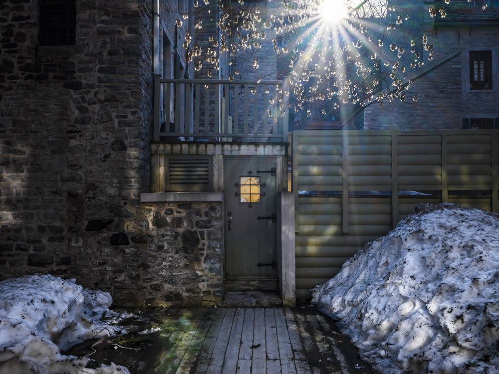 Light from the sun and the door's window cast highlights on the snow in Old Town Quebec