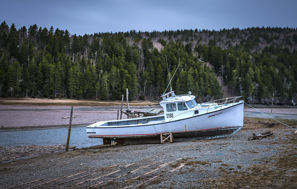 Across the road from where I filled up with gas, a boat sits idle at low tide east of St. John