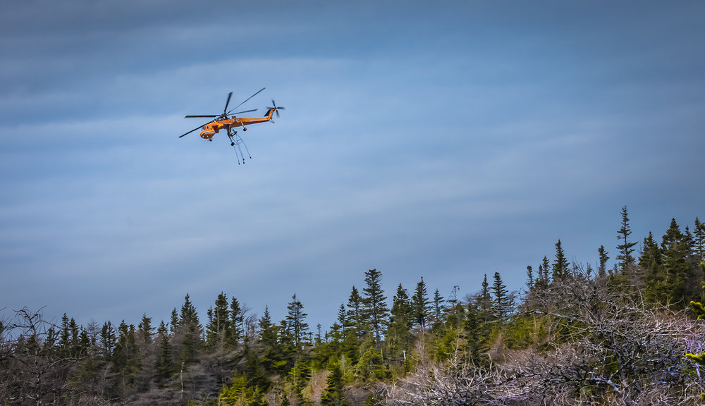 Just after delivering another transmission tower, the helo returns to pick up another, a few kilometres away.