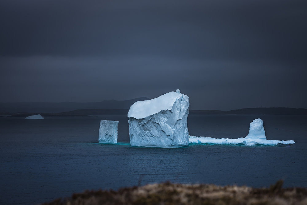 On a dark coud day, eventually the spot of sunlight moves over the water and lights up this huge iceberg at the end of a difficult hiking trail.