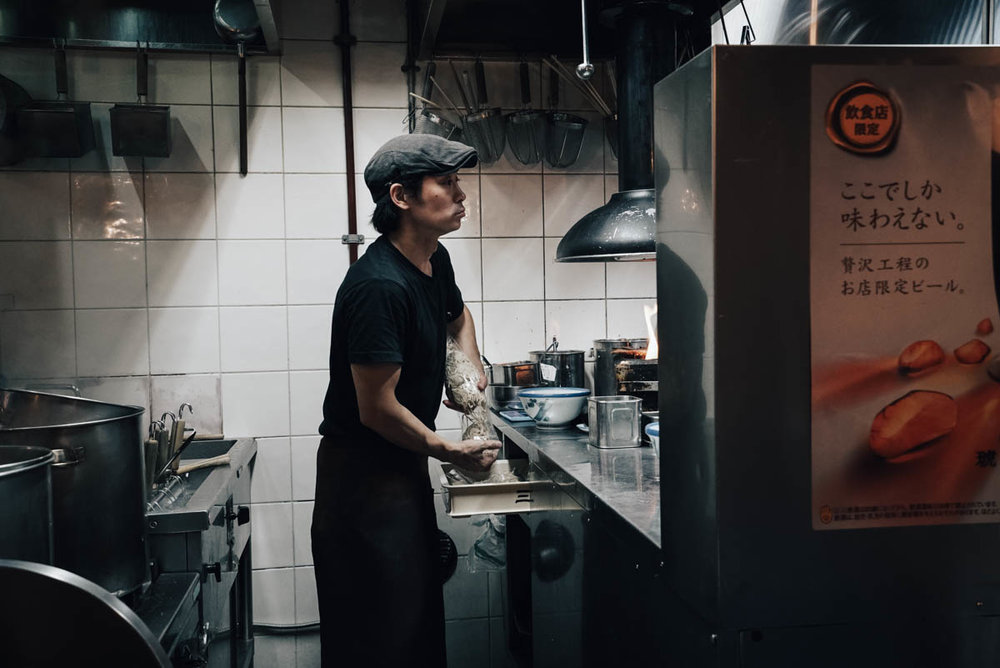 Afuri Ramen, Tokyo. I find that I tend to miss the intimacy of a 55mm or 85mm in crowds where I won't be able to focus so closely on people discreetly with a 35mm. Here the counter was just in front of the kitchen hence got a tight enough frame of the action.