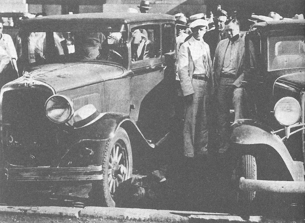 The bullet-riddled smoking ruins of the law enforcement car – with the bodies of the slain men still inside.