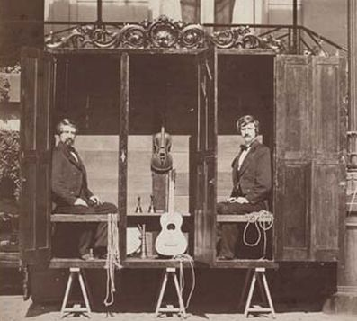The Davenport Brothers in their famous spirit cabinet