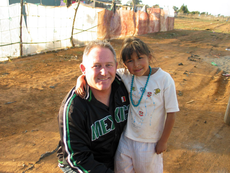 Gary with a young Mexican girl after building a home for her family.