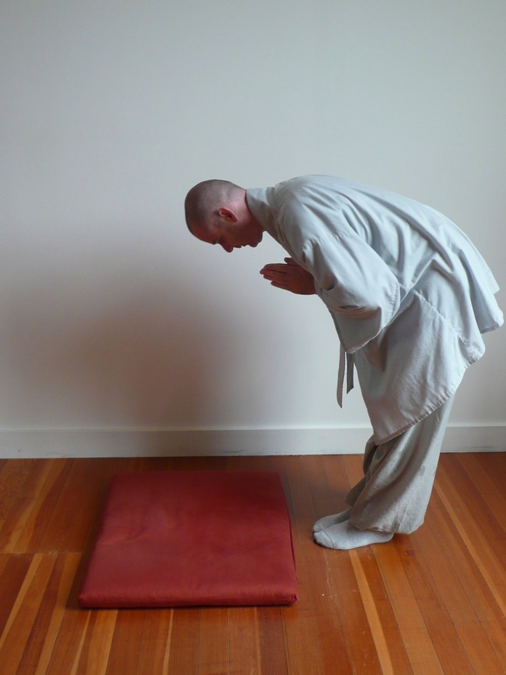 2. Bow fully from the hips, keeping your back straight so your chest is parallel to the floor. Your head should be bowed and your hands should remain close to your body. -