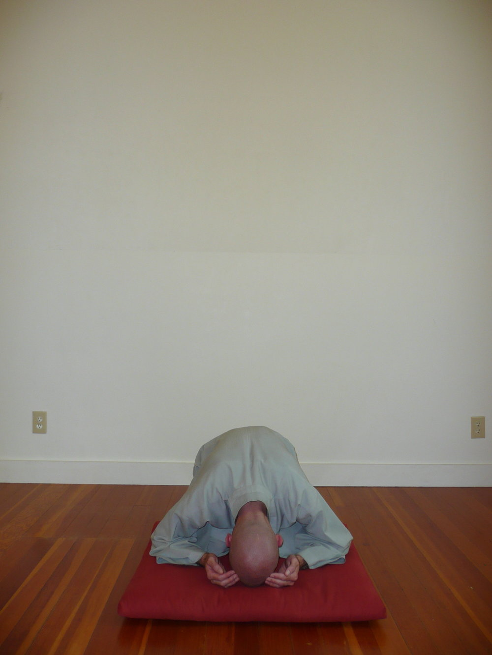 4. Rock back and down so that your rear is touching your heels and your forehead is touching the floor. In this position, your hands should be turned over (palms up), touching the mat next to your ears and your left foot should be crossed over the right one. Remain for a moment in this position. -