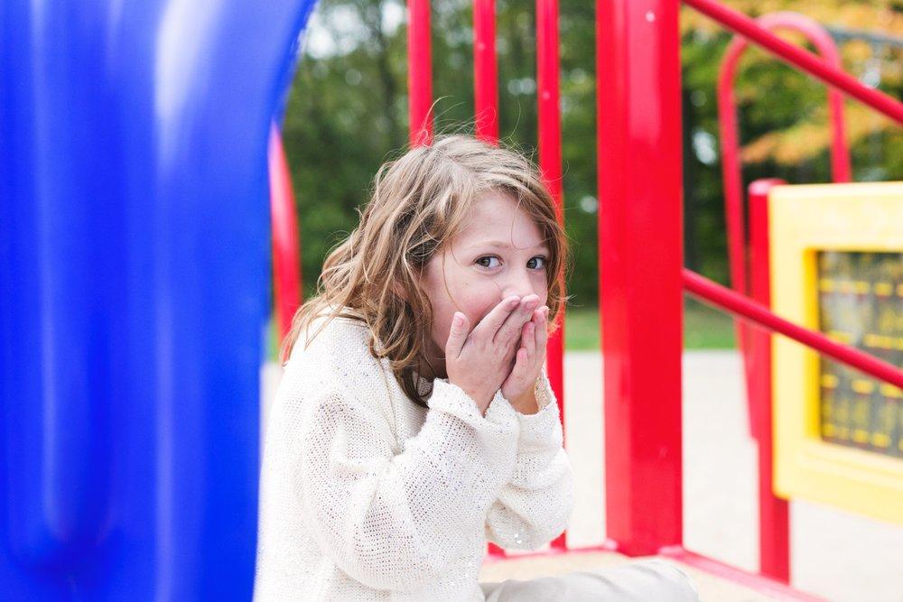 little-girl-laughing-behind-hands_4460x4460.jpg
