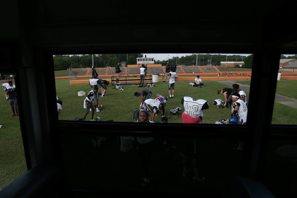"""Players get ready outside of Orange High School's football stadium. As a JV team, they don't usually get into locker rooms, creating a bonding experience when they all put on their gear together outside. """"We built a brotherhood this year and that's really important. We played for each other,"""" said Jeffrey Monroe, a junior halfback."""