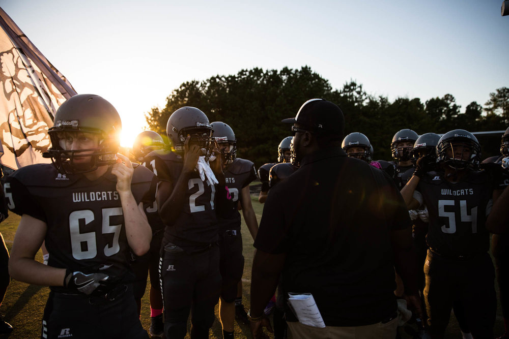 """Players gather before the homecoming game kickoff for a last minute rally speech. """"We came together as a team and family and got things done this year,"""" said Butler."""