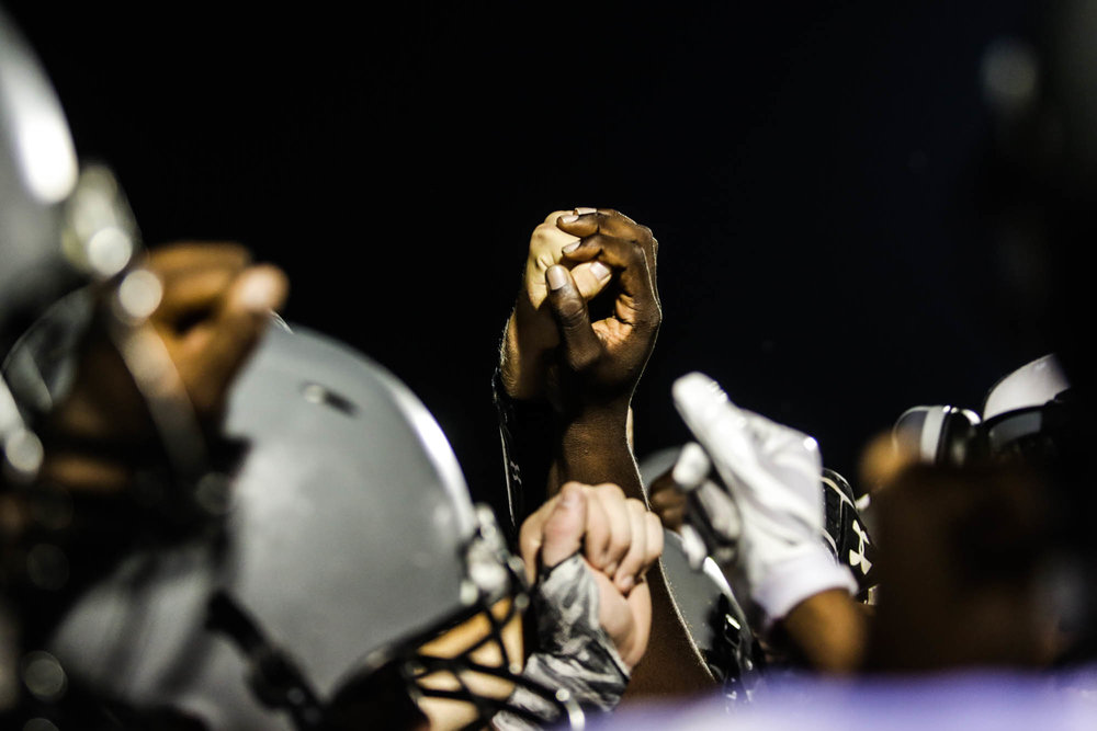 """Players grasp hands before a home game. """"I'm pretty confident about next season because we actually had a strong team this year. If we keep staying together and hit the weight room we could actually get stronger, actually compete,"""" said Farrow."""