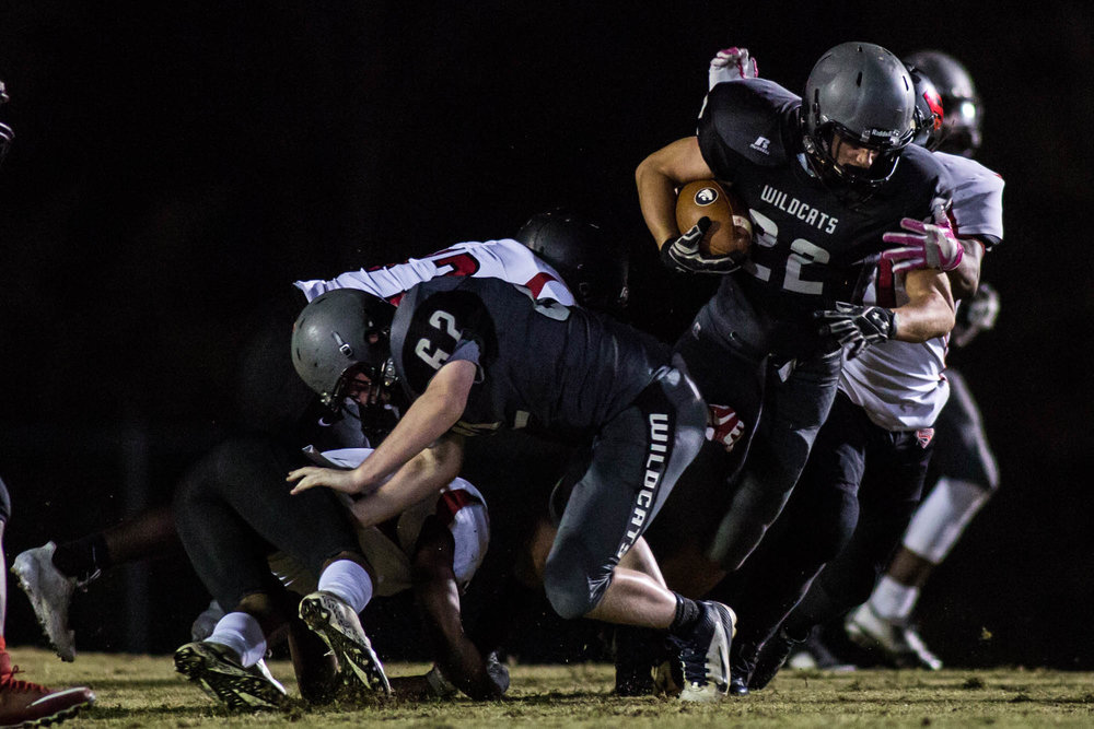 """Grayson Clements, a junior halfback, runs the ball in a home game against Southern Durham. The Wildcats barely won, 21-20. """"Against Southern, scoring the go ahead extra point was pretty cool, especially because kickers don't usually get to do much,"""" said Butler."""