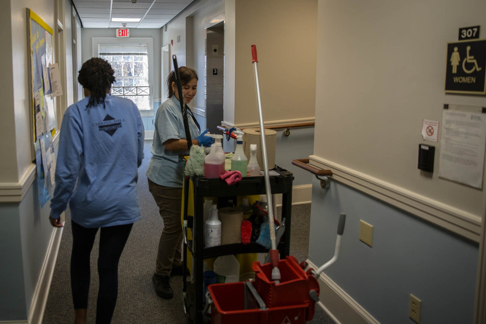 """Lwin gives a soft smile to a student passing her in the hallways while cleaning. """"Its good, I like the UNC housekeeping because it's close to my house,"""" she said """"In 2007 we moved to Chapel Hill because we wanted to work here. [The students] are nice."""""""