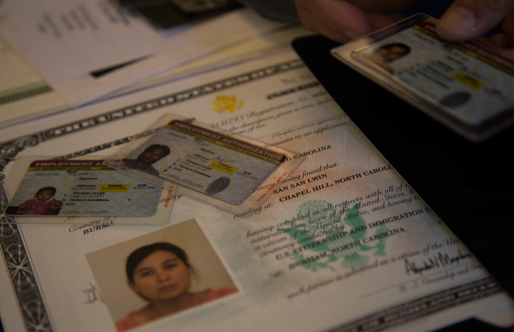 """Lwin shows a meticulously kept collection of documents telling her journey to becoming an American citizen. She even has the plastic bag with the IOM logo given to refugees. """"I want to keep, this is my life. We can't speak any English when we came to the United States,"""" she explained. """"In the United States, every airport knows [the bag we carried with documents] and knew we were refugees. It's crazy."""""""