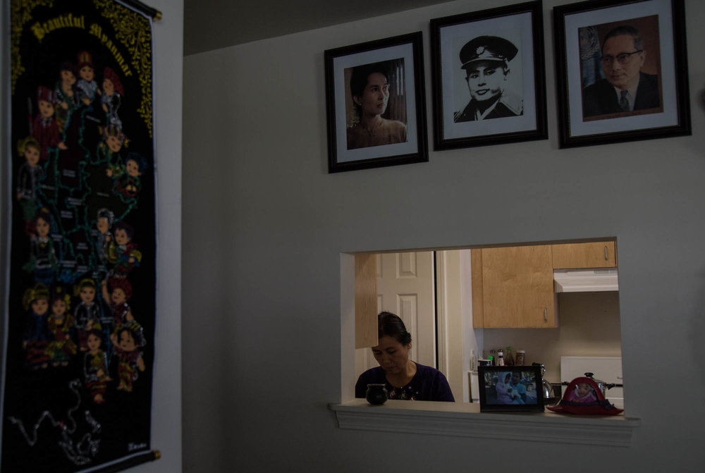 """Lwin prepares food in her house. The family applied for a Habitat for Humanity house in 2014, which they now decorate with mementos of Myanmar. Photos of Burmese leaders and humanitarians line the walls, along with photos of family, and a framed certificate for a C. Knox Massey Distinguished Service Award, one of UNC-Chapel Hills highest honors that Lwin won. """"Our house is small,"""" Lwin said, """"but it is good."""""""