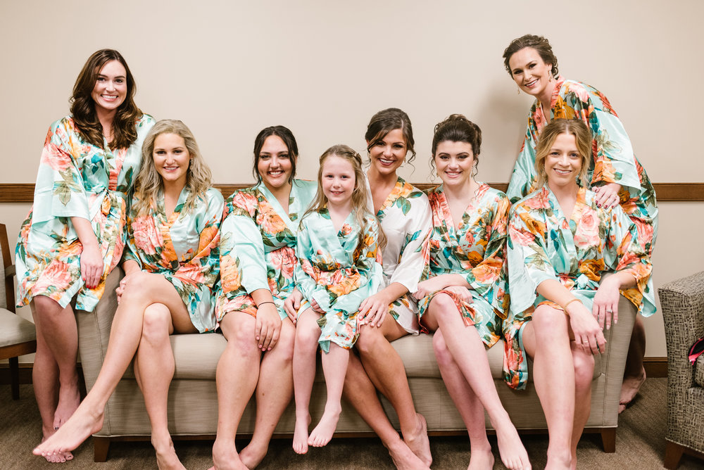 bride and bridesmaids on couch posing for picture