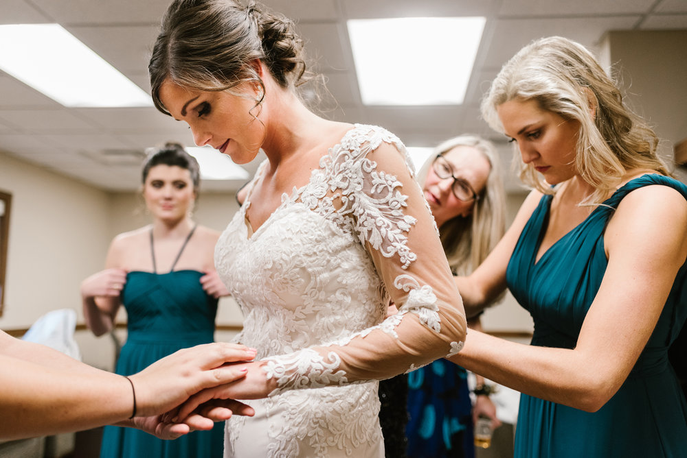 bridesmaids getting bride into wedding dress